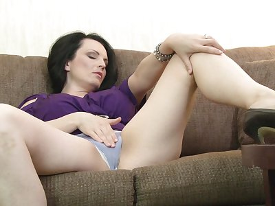 Busty brunette chick Stacy Ray enjoys masturbating on the sofa